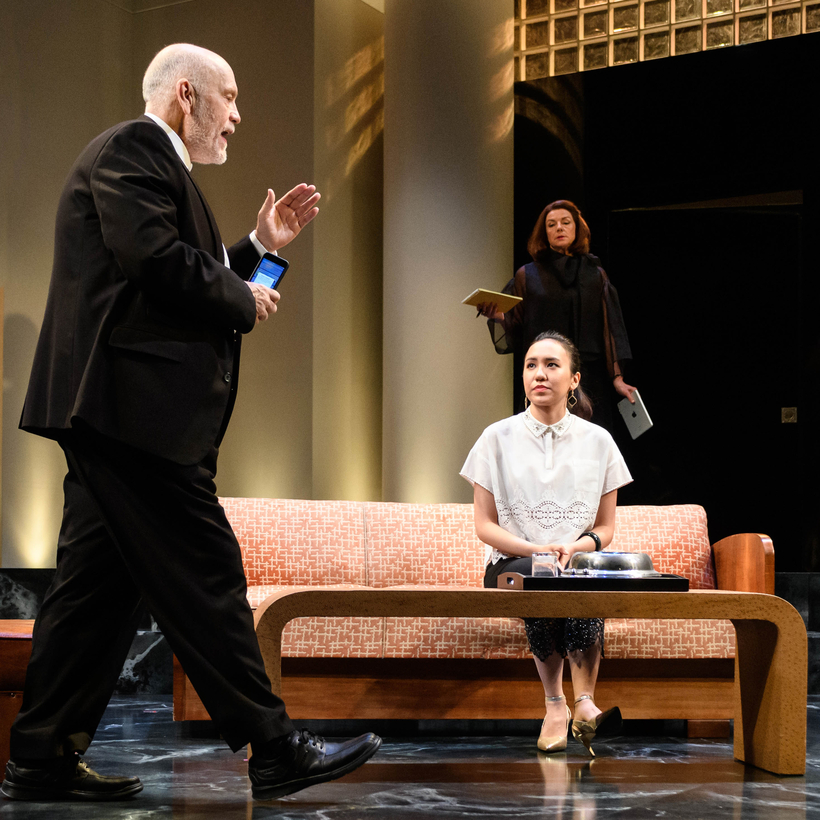 John Malkovich as Barney Fein and Ioanna Kimbook as Yung Kim Li (behind her, Doon Mackichan as Sondra) in Bitter Wheat, at the Garrick Theatre, London, June 2019.
