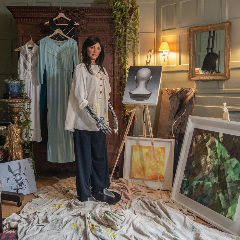 Putting the art into artificial intelligence: Ai-Da with some of her paintings.