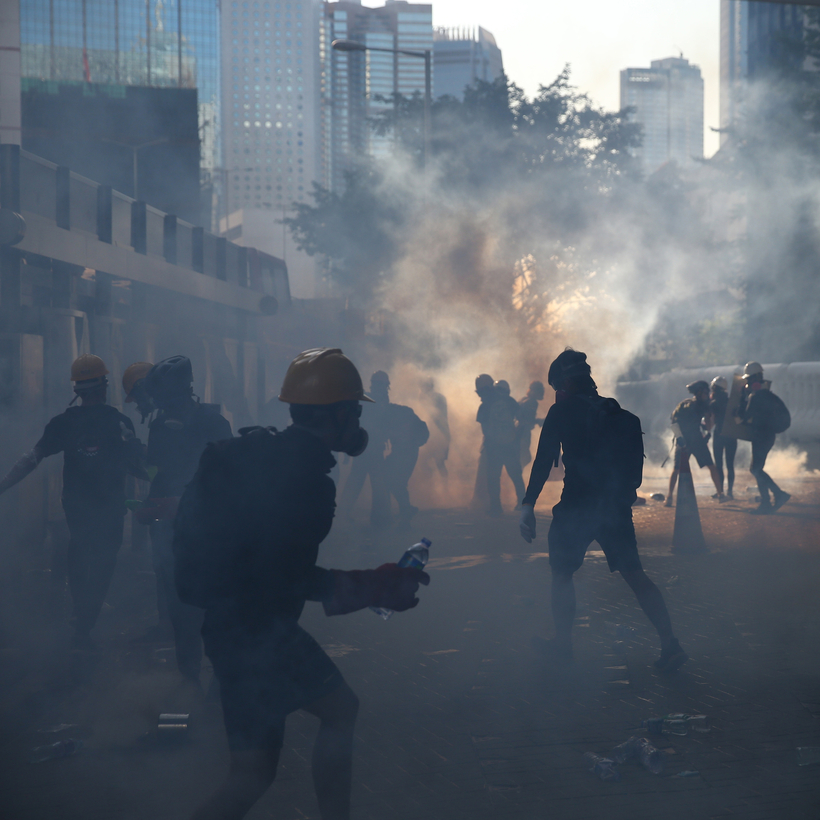 Protesters in Hong Kong react after police fire tear gas at them, August 2019.