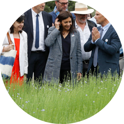 "Paris' mayor Anne Hidalgo (C) reacts during the inauguration of the ""BiodiversiTerre"" garden, at the foot of the Arc de Triomphe on June 3, 2017 in Paris. A farm and its sheep, a field of linen, 130 trees and silkworms: the prestigious avenue Foch in Paris will host biodiversity this weekend with BiodiversiTerre, a ""plant work"" of 10,000 m2 in the form of ""agricultural and horticultural walk"", announced May 30 by the mayor of Paris"