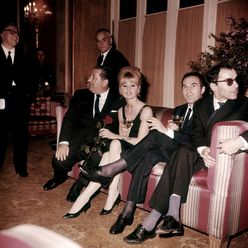 Brigitte Bardot attends the opening of Contempt in Rome with, to her left, actor Michel Piccoli and director Jean-Luc Godard. The author Alberto Moravia stands behind the couch.